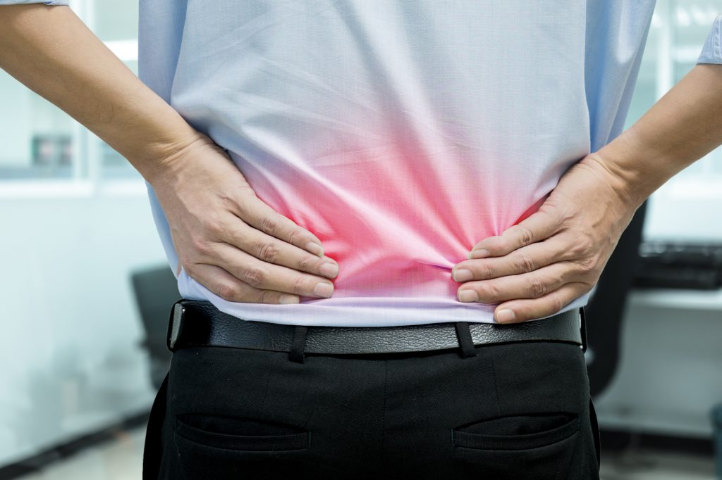 Representing A man in blue shirt feeling pain on his back. Office syndrome. Back pain from work. Herniated nucleus pulposus. spine pain. spinal degeneration.